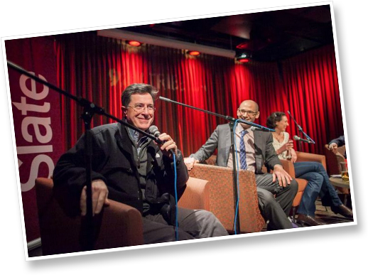 Stephen Colbert smiling behind a microphone at a Slate event.